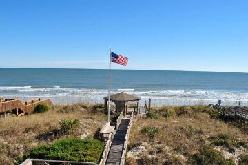 American Flag flying from gazebo on walkway to the beach
