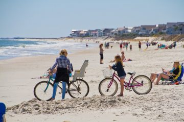 family on bikes on the beach